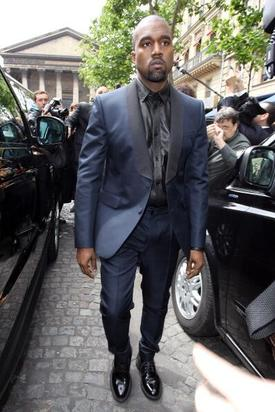 Kanye looking daper in a metallic navy blue suit and black button-up
