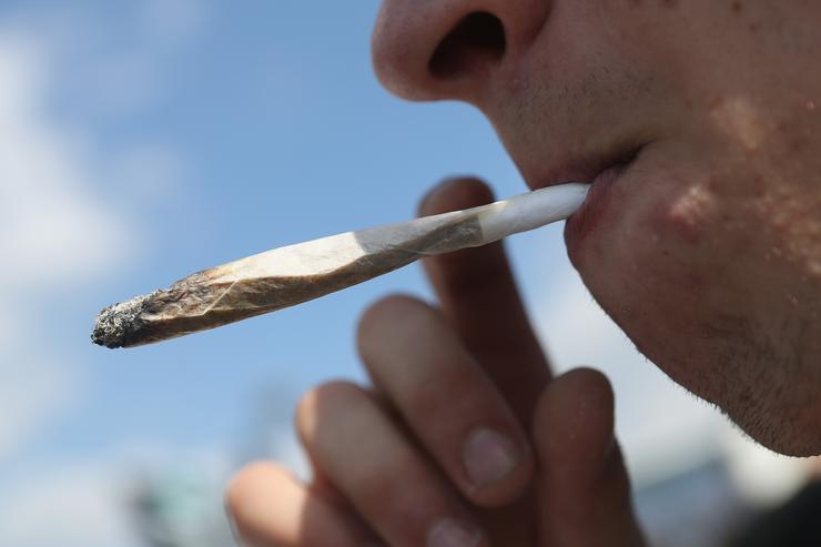 An activists smokes a marijuana joint prior to marching in the annual Hemp Parade (Hanfparade) on August 13, 2016 in Berlin, Germany. German proponents of cannabis legalization are hoping that the legalization in several states in the USA in recent years will increase the likelihood of legalization in Germany.