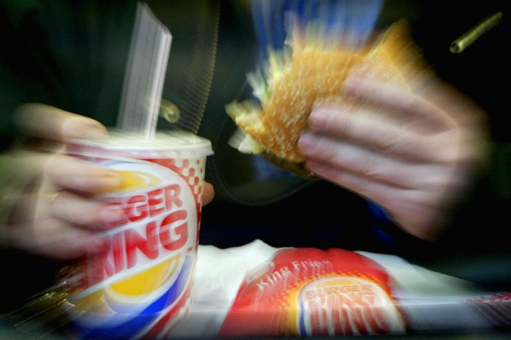 A man eats his lunch at a Burger King restaurant December 13, 2002 in London. Diageo PLC, the world's largest liquor company, has finalized the sale of its chain of fast-food outlets to a private consortium led by Texas Pacific in a deal worth $1.5 billion USD.